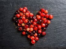 Heart made of cherry on black slate. Top view. High resolution product Stock Photo