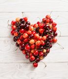 Heart made of cherry on white wooden table. royalty free stock images