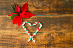 Heart made of Christmas canes with red and green leaves Stock Photo