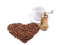 Heart made of coffee beans. Composition of heart made of coffee beans and coffee grinder Stock Images