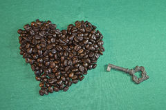 Heart made with coffee beans and ancient key Royalty Free Stock Image