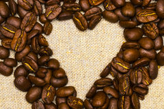 Heart made with coffee beans stacked against burlap canvas Stock Photo