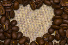Heart made with coffee beans stacked against burlap canvas Royalty Free Stock Images