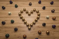 A heart made of coffee capsules. Tilt view with wooden background Stock Photography