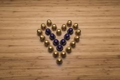 A heart made of coffee capsules. Tilt view with wooden background Royalty Free Stock Photo