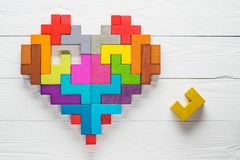 Heart made of colorful wooden shapes, top view, flat lay. Health background concept. Logical tasks. Conundrum, find the missing piece of the proposed Royalty Free Stock Photos