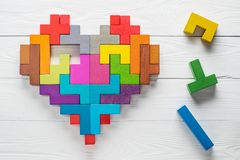 Heart made of colorful wooden shapes, top view, flat lay. Health background concept. Logical tasks. Conundrum, find the missing piece of the proposed Stock Photos