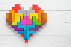 Heart made of colorful wooden shapes, top view, flat lay. Stock Photo