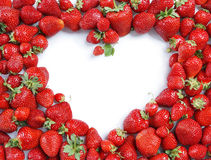 Heart made from deluxe strawberry on white background. Stock Photos