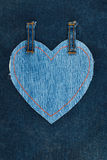 Heart made of denim fabric with yellow stitching on dark denim Royalty Free Stock Photos