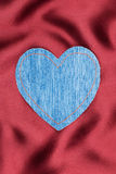 Heart made of denim fabric with yellow stitching on red silk Royalty Free Stock Images