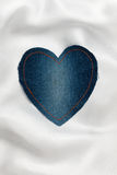 Heart made of denim fabric with yellow stitching on white silk Royalty Free Stock Photos