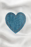 Heart made of denim fabric with yellow stitching on white silk Royalty Free Stock Images