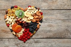 Heart made of different dried fruits and nuts on wooden background, top view. Space for text stock image