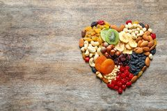Heart made of different dried fruits and nuts on wooden background, top view. Space for text royalty free stock photography