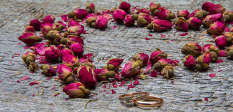 Heart made of dried flowers, buds of roses and two gold rings Stock Photos