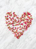 Dried rose flowers heart on marble background royalty free stock photography
