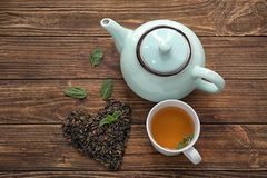 Heart made of dry green tea leaves and cup of aromatic beverage on wooden table royalty free stock images