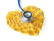 Heart made of fish oil capsules with stethoscope. On white background stock photos