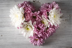 Heart made of flowers on the white wooden background top view Royalty Free Stock Image