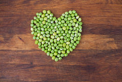 Heart made of fresh locally grown green peas on wooden background Stock Image