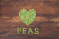 Heart made of fresh locally grown green peas on wooden background Royalty Free Stock Photography