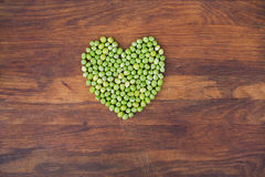 Heart made of fresh locally grown green peas on wooden background Stock Images