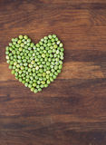 Heart made of fresh locally grown green peas on wooden background Royalty Free Stock Image