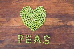 Heart made of fresh locally grown green peas on wooden background Stock Photo