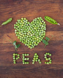 Heart made of fresh locally grown green peas on wooden background Stock Photos