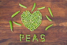 Heart made of fresh locally grown green peas on wooden background Stock Photography