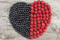 Heart made from fresh raspberries and blueberries on wooden background. Healthy nutrition. And diet Stock Photos