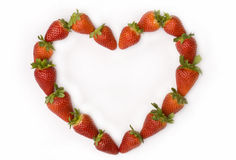 Heart made with fresh strawberries. On white background stock photography