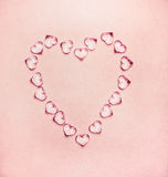 Heart made from glass hearts on pale pink background Royalty Free Stock Images