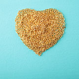 Heart made with gold chain wood texture Royalty Free Stock Photo