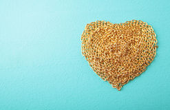 Heart made with gold chain wood texture.  royalty free stock photo