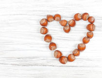 Heart made of hazelnuts on wooden background. Stock Photography