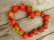 Heart made of Juicy strawberry. Lying on a wooden table Royalty Free Stock Photography