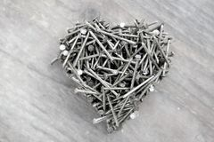 Heart made of nails, for father`s day, anniversary or Valentine. Lots of nails and put together in a heart shape, processed with a silvery filter, top view Stock Photo