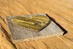 Heart made of nails on wood with wowen gold string Royalty Free Stock Photo