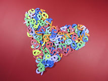 Heart made from numbers. Small colored foam cut numbers arranged to form the shape of a human heart , on red background royalty free stock photos