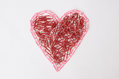 Heart made of office paperclips Stock Photos