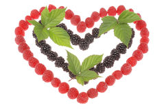 Heart made out of raspberries and blackberries. Top leaves of bl Stock Photo