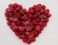 One ripe red heart-shaped raspberry over white backgroung. Heart made out of raspberries over white background Royalty Free Stock Photo