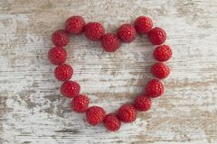 Heart made out of raspberries over white wooden background. Red Heart Made of Raspberry Stock Photos