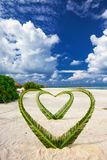 Heart made of palm tree leaves on tropical island with overwater bungalows in the background.  royalty free stock images