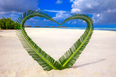 Heart made of palm tree leaves on tropical island with overwater Royalty Free Stock Image