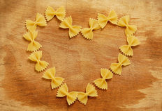 Heart made with pasta. Italian farfalle pasta forming a heart on wood background Stock Photography
