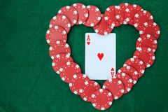 Heart made with poker chips, with an ace of hearts, on a green background table. Top view with copy space stock photos