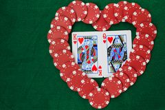 Heart made with poker chips, with king and queen of hearts, on a green background table. Top view with copy space royalty free stock image